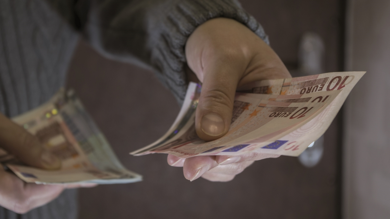 A woman in gray knit sweater holds out three ten-euro bills with her left hand against brown front door. Concept: payment with the installer, plumber or electrician for maintenance made in apartment